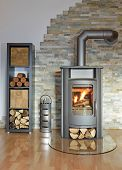 stock photo of cozy hearth  - burning wood fired stove with fire - JPG