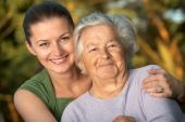 stock photo of old lady  - Woman in her late twenties embracing a senior lady - JPG