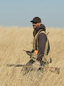 stock photo of hunters  - A hunter in tall grass hunting pheasants - JPG