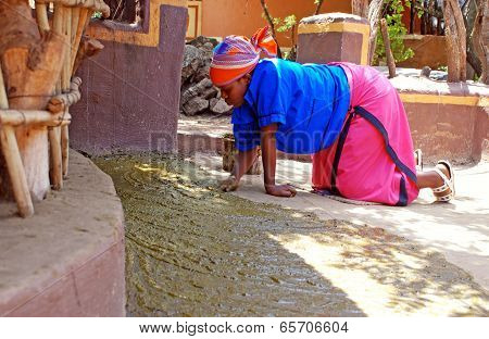 African Woman Covered Floor Of House In Manure