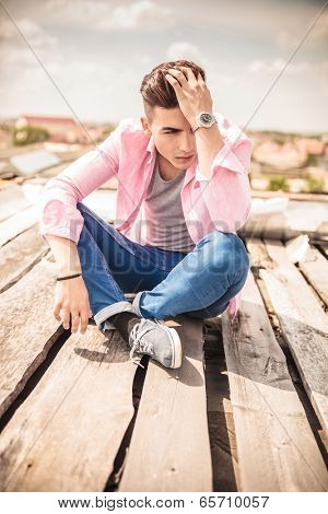 serious young man is sitting and fixing his hair , outdoor picture