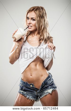 Sexy athletic woman drinking caffe latte in wet clothes on gray background