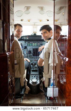 Portrait of confident pilot and copilot in corporate plane cockpit