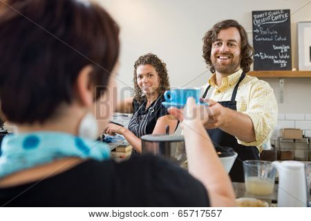 Happy barista serving customer cup of coffee