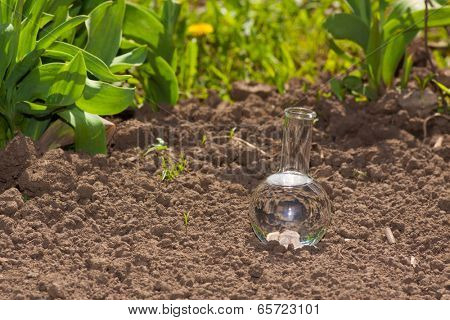 flask with clear water or fertilizer on dry soil