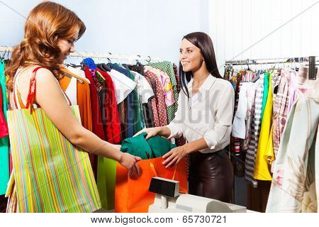 Woman with purchase after paying at cashiers desk