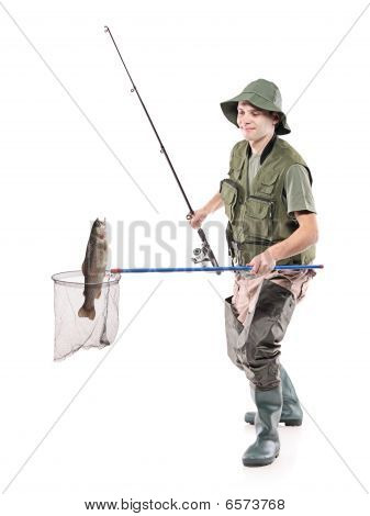 Young fisherman putting a fish into a fishing net