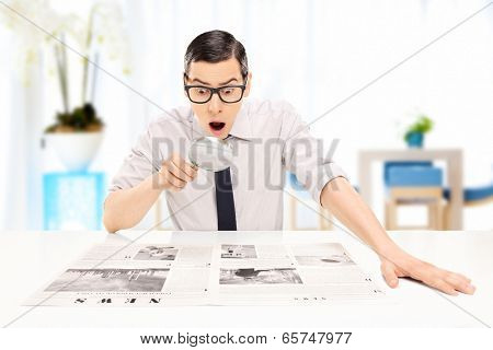 Surprised man reading the news with scrutiny in an office