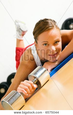 Woman with dumb bell in the gym