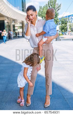 Business mother speaking over the cellphone, with two kids