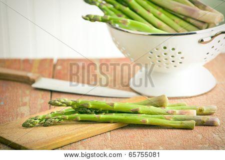 green asparagus in colander on old wooden background