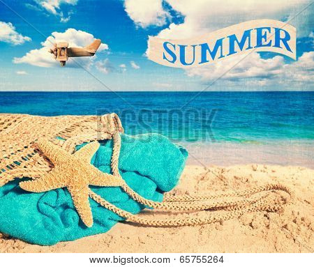 Beach bag and towel with banner over the ocean advertising summer - vintage tone and texture added