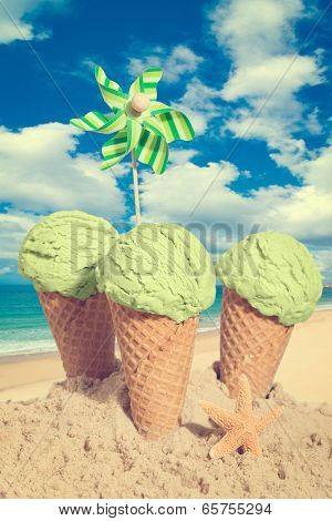 Mint ice cream cones in the sand against a summer sky - vintage tone effect added