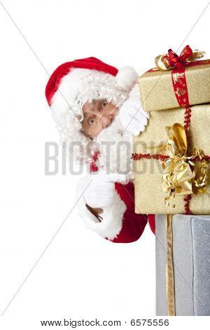 Santa Claus Is Hiding Behind Christmas Gift Boxes And Pointing On Them