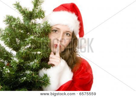 Young Attractive Santa Claus Woman Beside Christmas Fir Tree Puts Finger On Lips
