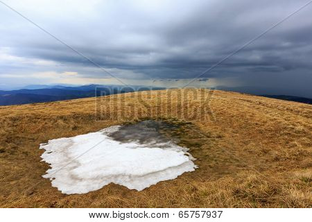 last snow on meadow in mountains on thunderstorm sky background