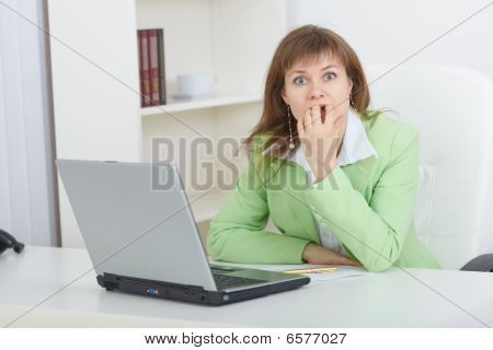 Scared Woman Sits On Workplace With Laptop