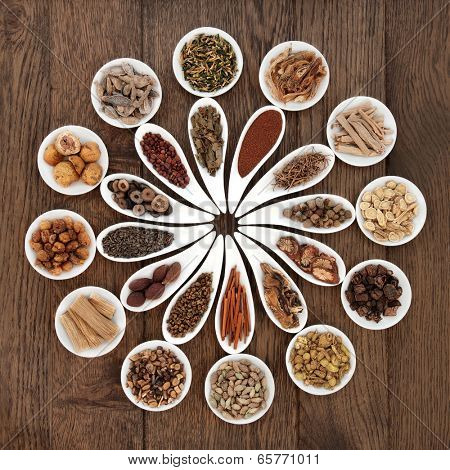 Large chinese herbal medicine selection in china bowls over old oak background.