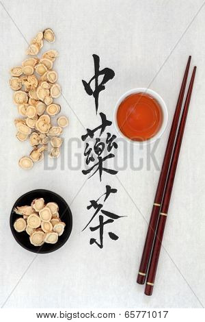 Chinese herbal tea calligraphy script on rice paper with astragalus herb, teacup and chopsticks. Translation of script reads as chinese herbal tea.