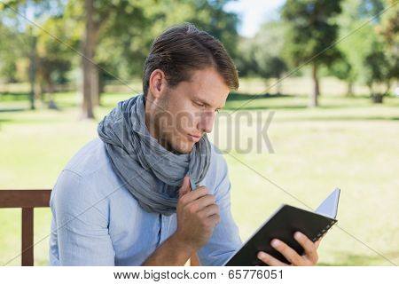 Stylish young man writing in his notepad on a sunny day
