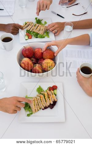 Workers eating healthy lunch during meeting in the office
