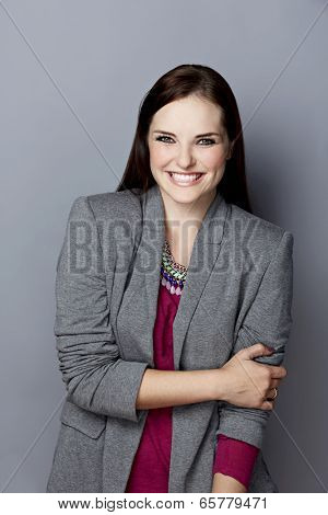 Portrait of a smiling young woman, with long brunette hair, on gray studio background, wearing pink purple top, gray blazer and bright statement necklace