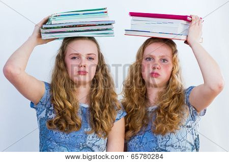 Two schoolgirls with textbooks on their heads