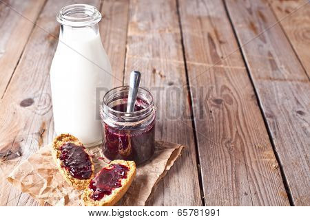 black currant jam in glass jar, milk and crackers on rustic wooden board