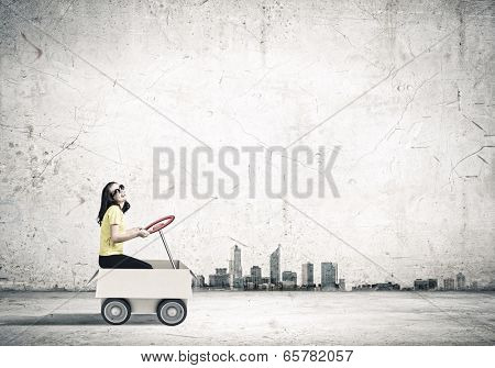 Young funny woman riding in carton box