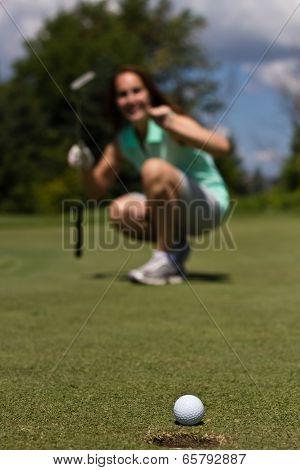 Woman Putting The Golf Ball Into The Cup - Selective Focus