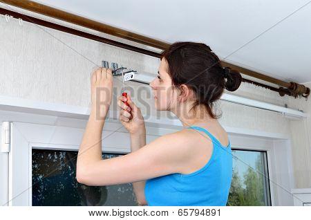 Girl Hangs Vertical Blinds, Tighten With A Screwdriver, Screw Brackets