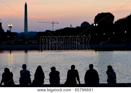 Sunset in Washington D.C. with silhouette of Washington Monument and people around Capitol Building reflection pool