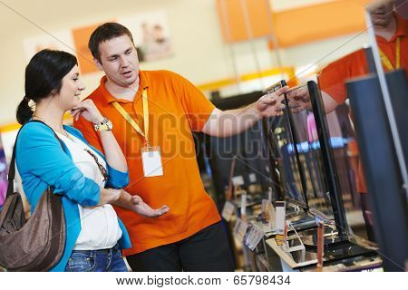 Young woman choosing tv set with shop assistant in home appliance shopping mall supermarket