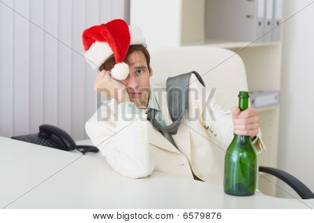 Young Man In Christmas Hat Cap With Bottle Sits At Table