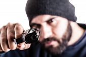 stock photo of gangsta  - a bearded criminal pointing a pistol and wearing a beanie hat isolated over white - JPG