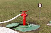 stock photo of manhole  - Red fire hydrant stands on roadside in manhole - JPG