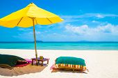 stock photo of recliner  - Beach chair and umbrella on a white sandy beach - JPG