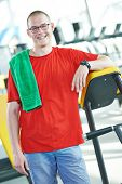 pic of triceps brachii  - Smiling athlete bodybuilder man in front of barbell weights in fitness gym - JPG