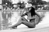 foto of jamaican  - Stock image of a young Jamaican woman posing by the pool - JPG
