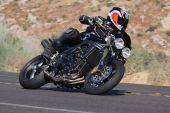 foto of crotch-rocket  - A speeding black motorcycle racing around  a corner in the country - JPG