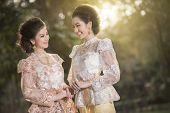 stock photo of polite girl  - Two beautiful girls getting dressed in Thai Traditional Costume - JPG