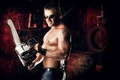 picture of man chainsaw  - Expressive handsome muscular man with a chainsaw in the old garage - JPG