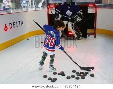 Young New York Rangers fan shooting the puck before Rangers season opening match in New York