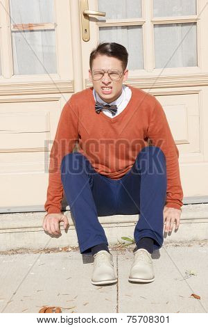 Angry  Handsome Man With Glasses And Sweater Sitting On Steps In Front Of House