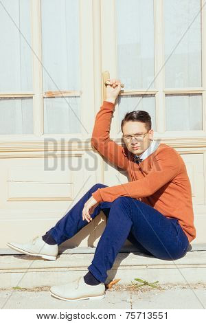 Serious Handsome Man With Glasses And Sweater Sitting On Steps In Front Of House