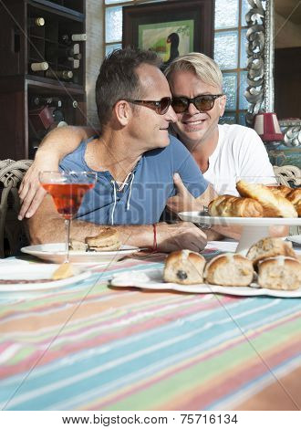 Happy attractive gay couple enjoying a morning breakfast