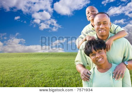 Happy Family Over Grass Field, Clouds And Sky