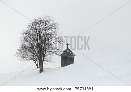 Winter landscape. Wooden chapel and a tree on a hill. The village is in the mountains. Carpathians, Ukraine, Europe