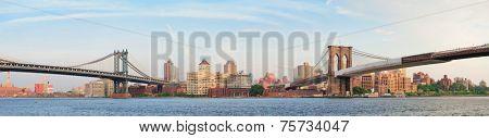 Manhattan Bridge and Brooklyn Bridge panorama over East River viewed from New York City Lower Manhattan waterfront at sunset.