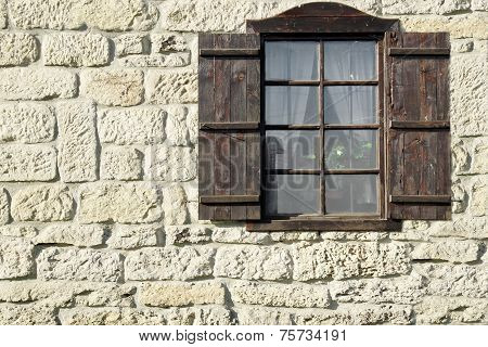 Vintage Single Window  With Wooden Shutters On Natural Stone Wall